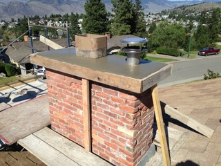 brick chimney with cement cap under construction