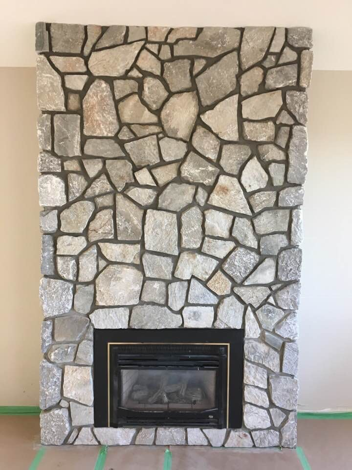 9.5 by 6.5 feet floor to ceiling residential fireplace finished in thin cut natural grey stone with a gas insert.